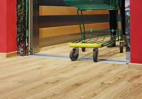 wineo Bodenbelag Holzoptik Braun im Geschäft mit Fahrstuhl und Einkaufwagen
