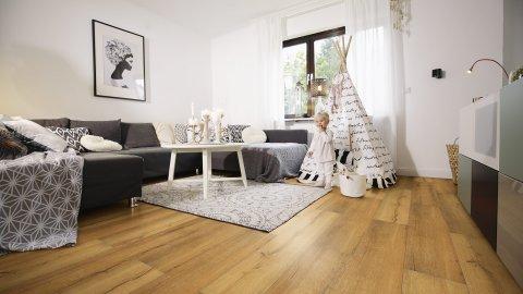 wineo Laminatboden im Wohnzimmer mit Sofa und Kind vor einem Zelt