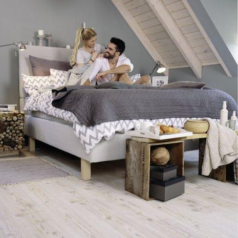 wineo Laminatboden im Schlafzimmer mit Bett und Paar