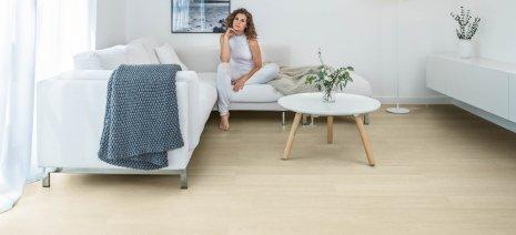 wineo Bodenbelag Hell im Wohnzimmer mit einer Frau auf dem Sofa