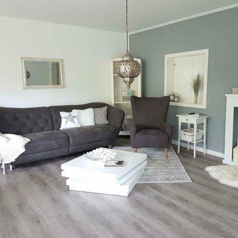 wineo Bodenbelag Holzoptik dunkel im Wohnzimmer mit Sofa und Sessel
