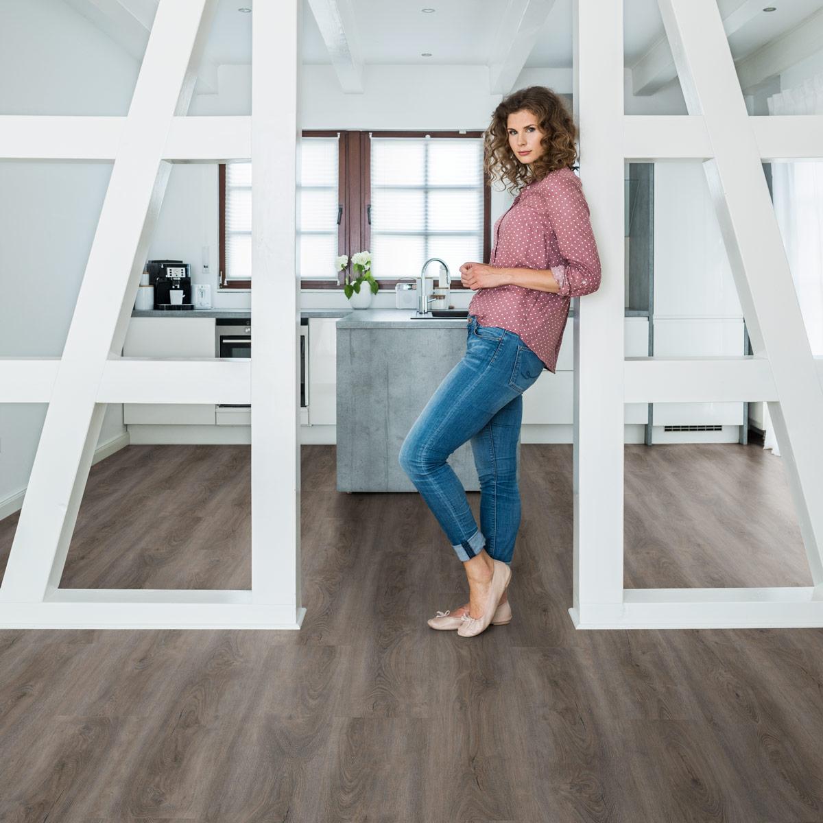 wineo Bodenbelag in der Küche mit einer Frau und Querbalken