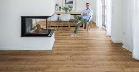 wineo Designboden mit einem Mann im Esszimmer und moderner Einrichtung