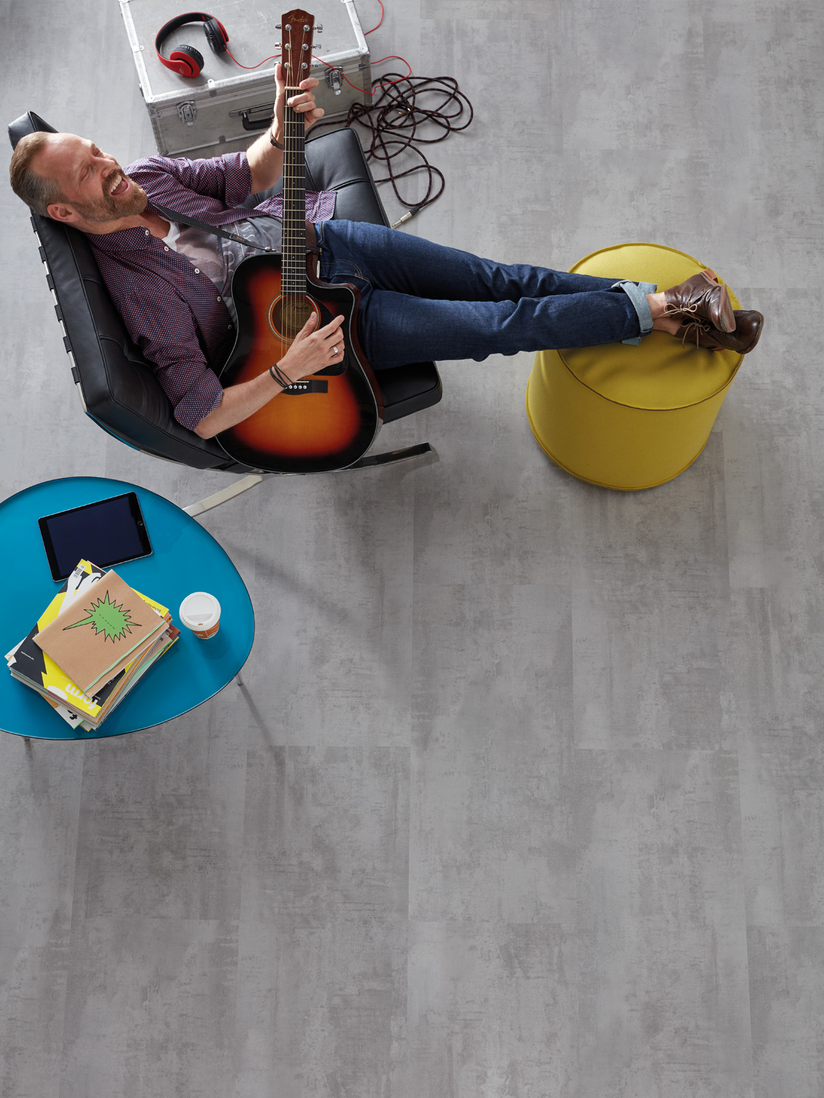 wineo Bodenbelag Mann auf Sessel Gitarre Kopfhörer