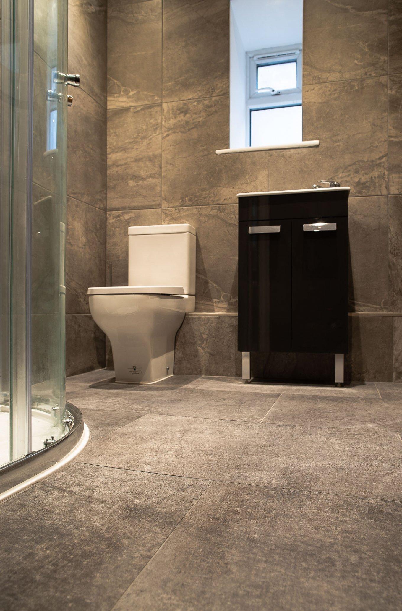 wineo Designboden im Badezimmer moderne Einrichtung Dusche Toilette graue Fliesenoptik