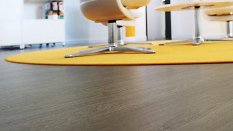 wineo Bodenbelag dunkle Holzoptik Büro Stuhl