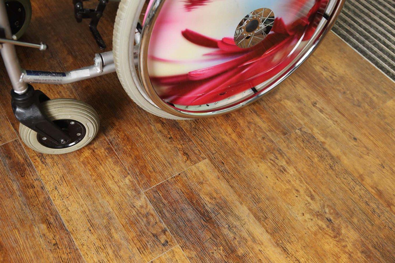 wineo Designboden im Seniorenheim Rollstuhl Holzoptik dunkel Vinylboden