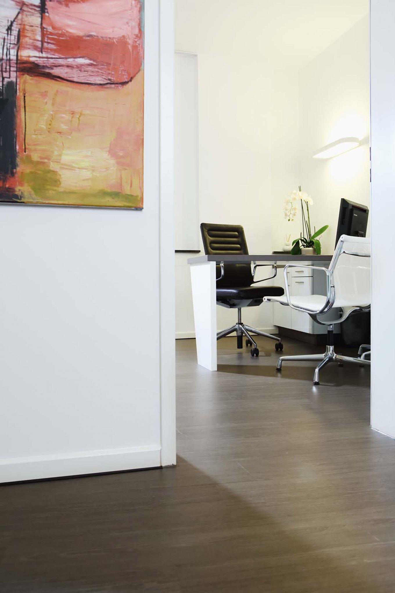 wineo Bodenbelag in Arztpraxis Bürostuhl Holzoptik moderne Einrichtung Praxisraum Behandlungsraum