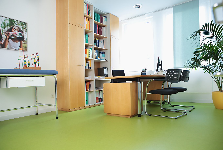 wineo PURLINE Bioboden Kinderarzt Praxis Behandlungsraum Schreibtisch Stühle Bodenbelag grün