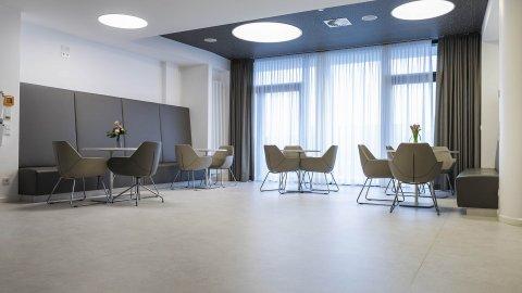 wineo Purline Bioboden Rollenware hell Wartebereich große Fenster Sitzmöbel braun modern Klinikum