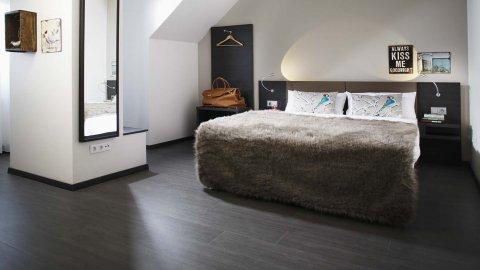 wineo Purline Bioboden dunkel Planken Bett Schlafbereich Hotel