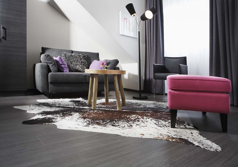 wineo Purline Bioboden dunkel Planken Teppich Sofa Sessel Farbaktzente Hotel